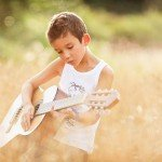 childrens-photographer-Nottingham - a boy playing his guitar in a cornfield