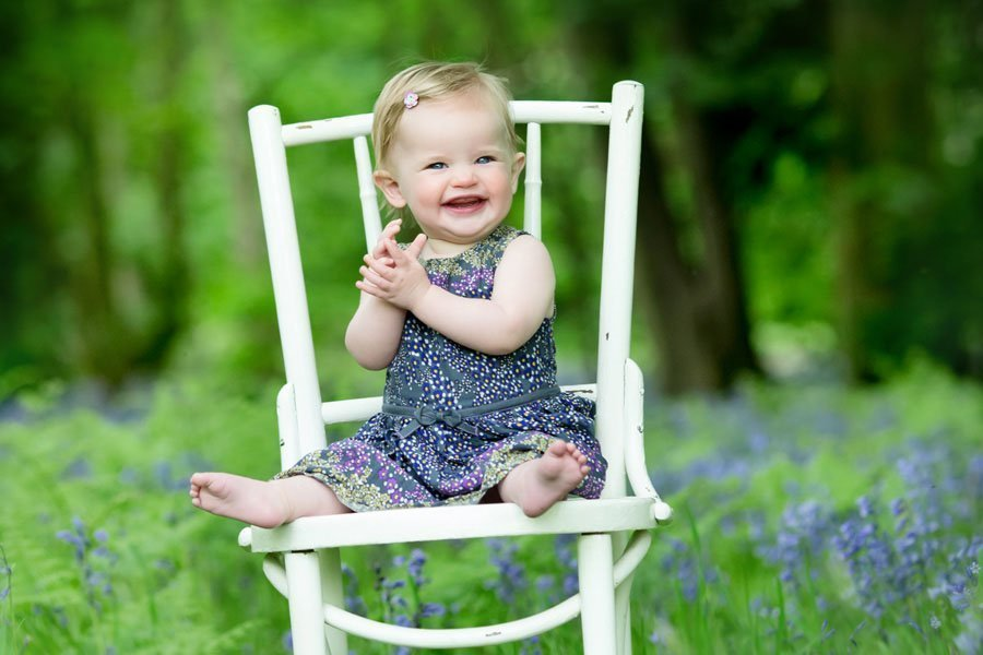 Baby girl sitting on chair in bluebell woods
