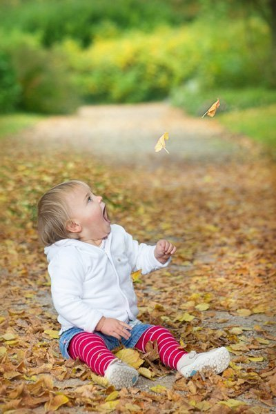 Family portraits nottingham happy girl looking at autumn leaves falling
