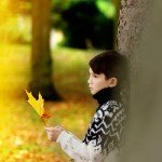 kids-photographer-nottingham - autumn portrait of boy holding leaf