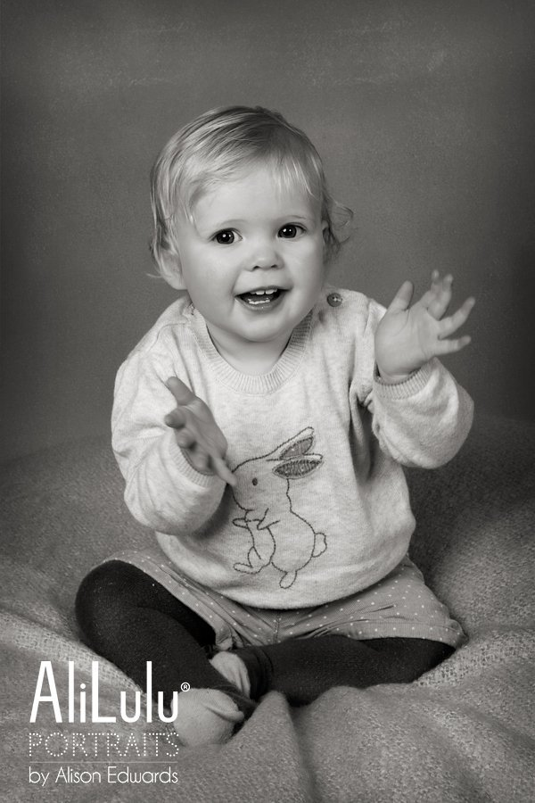 1 year old photo session of 1 year old girl clapping