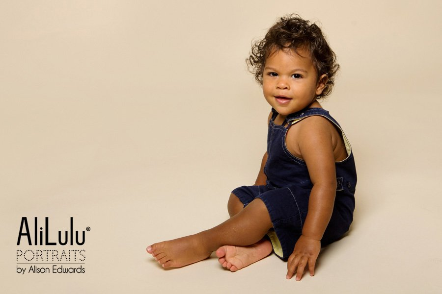 1 year old photo shoot boy in navy dungarees sitting down smiling
