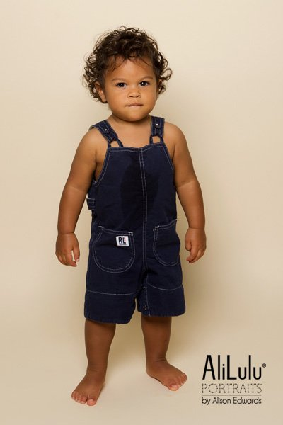 1 year old photo shoot studio portrait of boy in navy dungarees