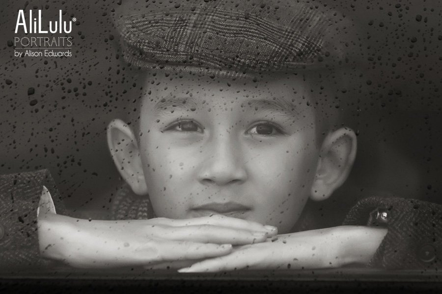 boy looking through window at rain