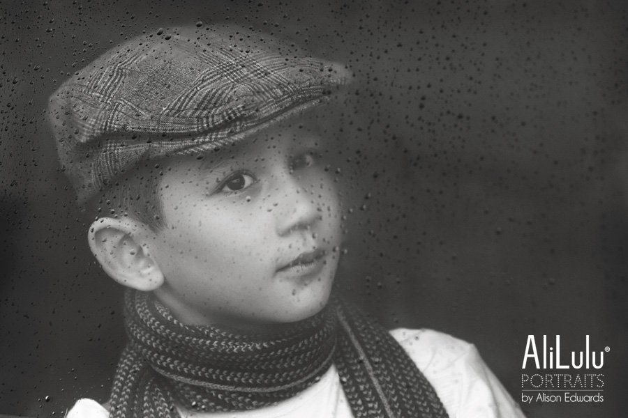 boy wearing flat cap and scarf looking through window with raindrops on