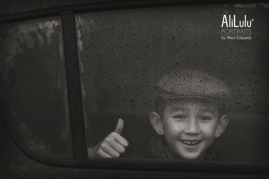 boy smiling with thumbs up rainy window