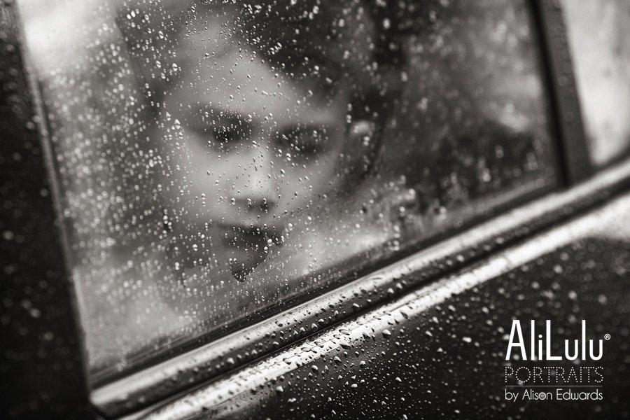 boy looking pensive through rainy window in car