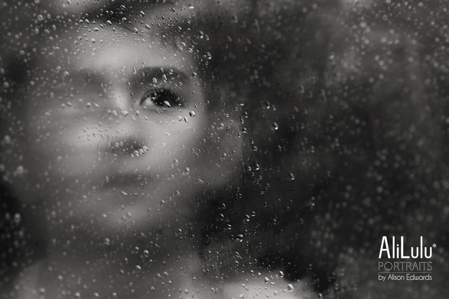 eerie photo of boy through through window with one eye visible