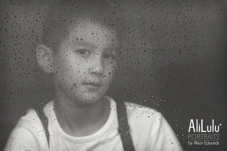 boy wearing braces looking through window on a rainy day