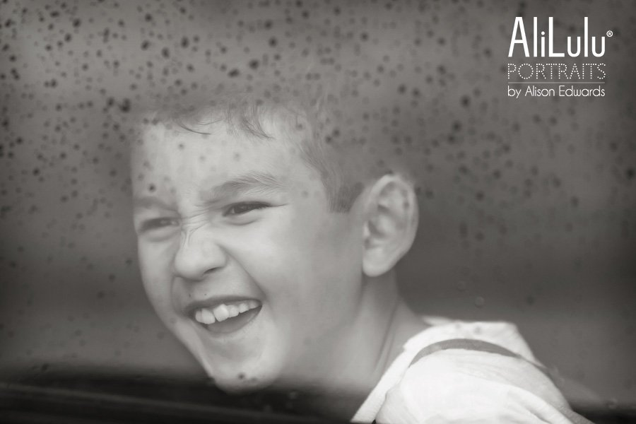 boy laughing looking out of rainy window
