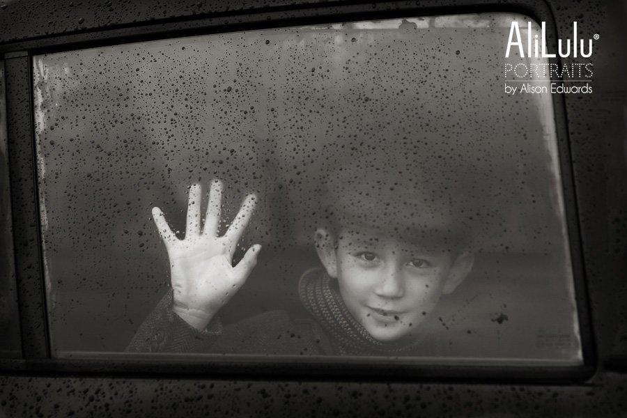 kids photos in the rain of boy wearing flat cap behind window pane