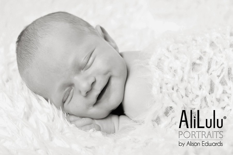 black and white photo of newborn baby girl smiling