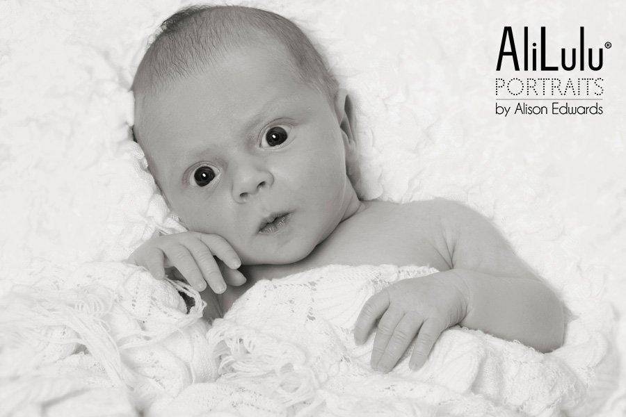 black and white photo of baby girl awake