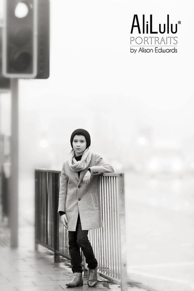 black and white portrait of boy in street on foggy day