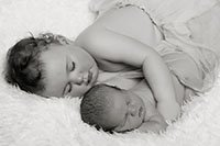 newborn baby girl and big sister sleeping side by side