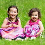 two young girls sitting in a field in pink dresses in Nottingham