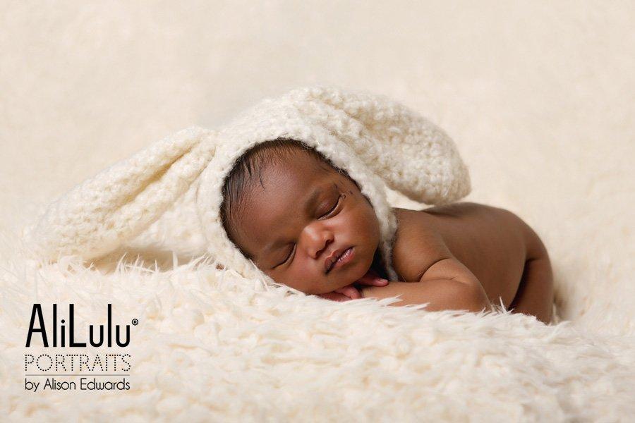 newborn baby girl wearing cream bunny ears hat