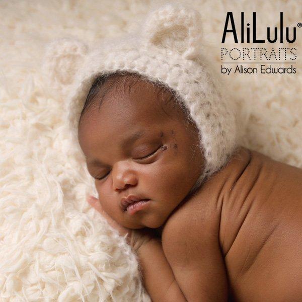 newborn baby girl wearing cream teddy bear ears hat