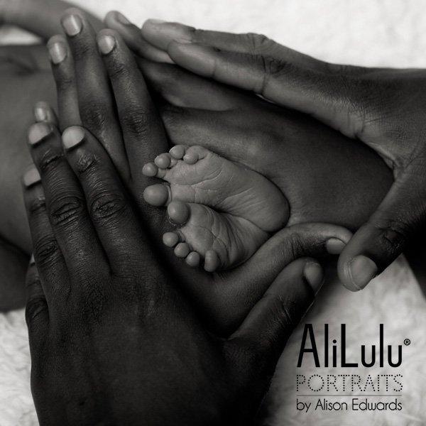 parents holding newborn baby's feet