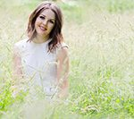 photo of girl in long grass wearing white dress