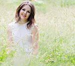 photo of girl in long grass wearing white dress