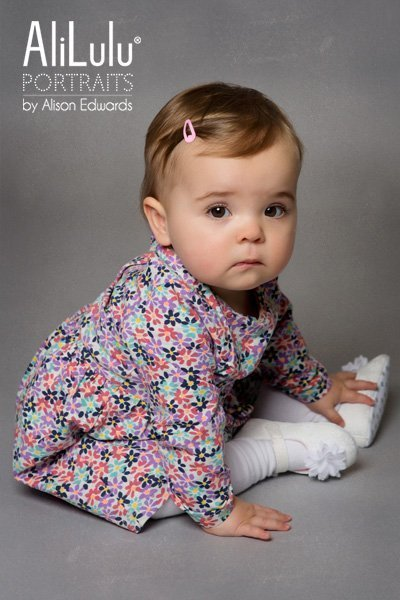 baby girl sitting to the side in flowered dress