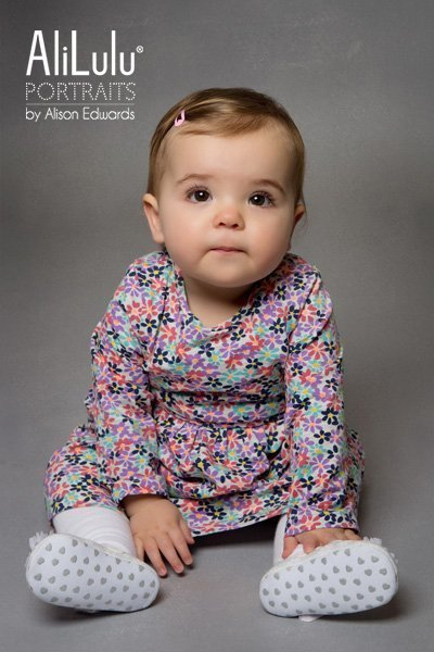 baby girl sitting looking forward in flowered dress