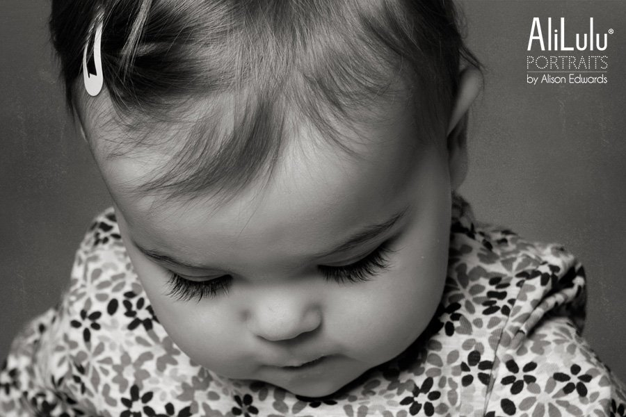 close up black and white photo of 1 year old girl looking down