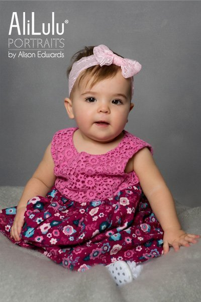 1 year old girl sitting wearing pink headband