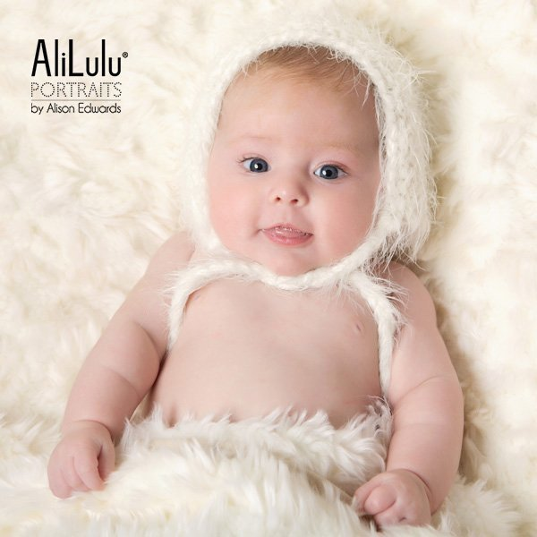 baby girl at 10 weeks old wearing cream hat
