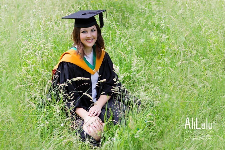 girl in graduation outfit sitting in long grass