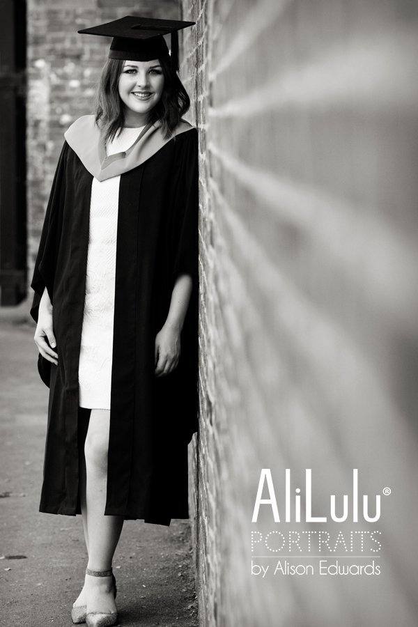 girl in graduation gown leaning against wall