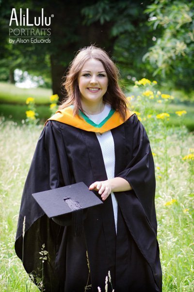 girl wearing graduation gown holding hat