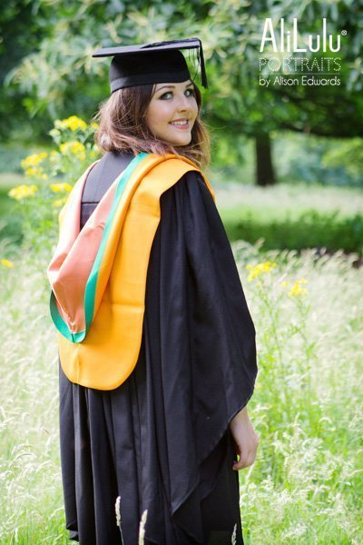 girl looking over shoulder wearing graduation outfit