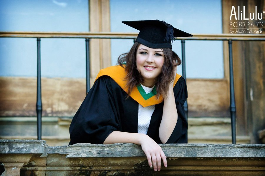 girl wearing graduation gown and hat looking over balcony