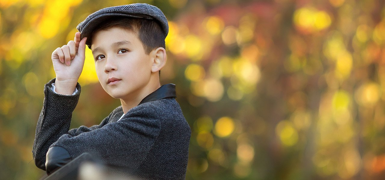 boy wearing flat cap in Nottingham park autumn season