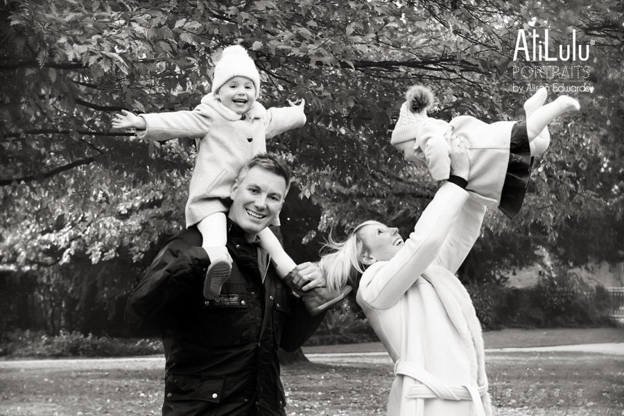 dad holding daughter on shoulders mum play throwing baby in air all smiling