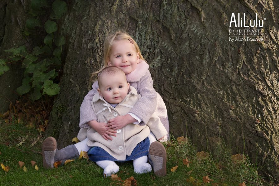 young girl cuddling baby sister next to tree