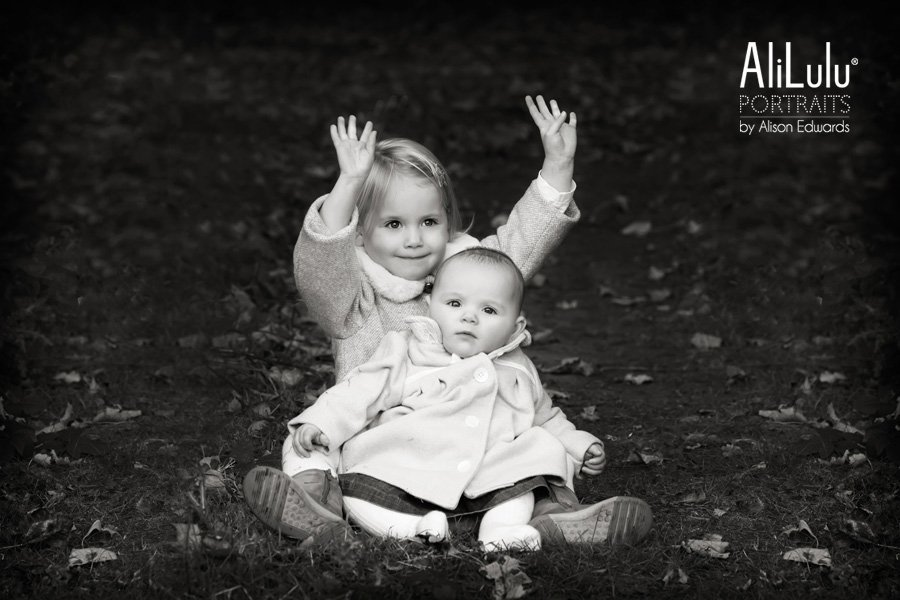 young girl and baby sister sitting on path in woodland waving