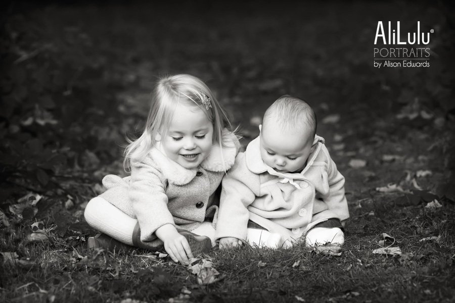 sisters playing with leaves in woodland park Nottingham family photographer