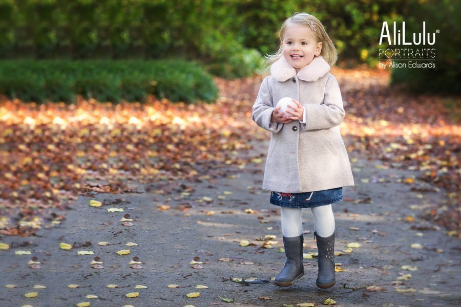girl jumping in park surrounded by Autumn leaves by Nottingham family photographer