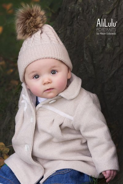 baby girl wearing bobble hat in autumn by Nottingham family photographer