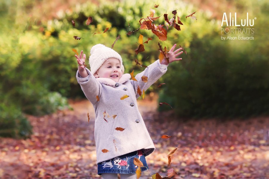young girl wearing hat throwing autumn leaves in Nottingham
