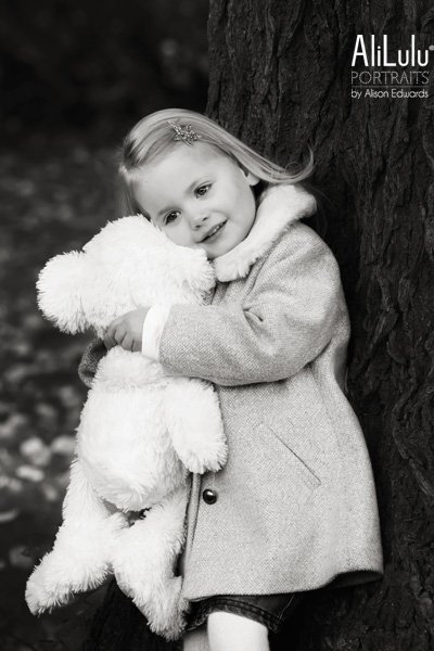 young girl cuddling teddy bear standing against tree Nottingham family photographer