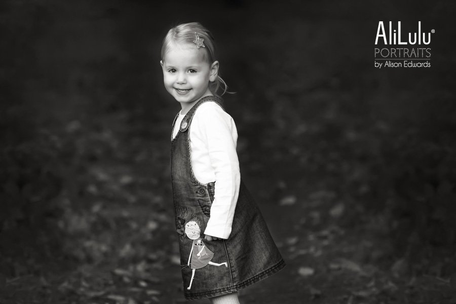 young girl smiling in woodland black and white photo