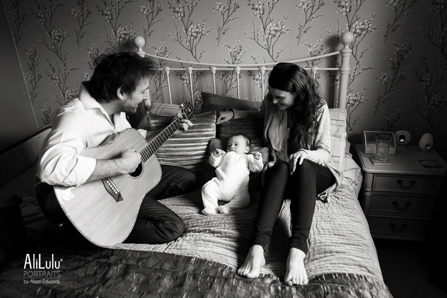dad playing guitar to baby on bed at home