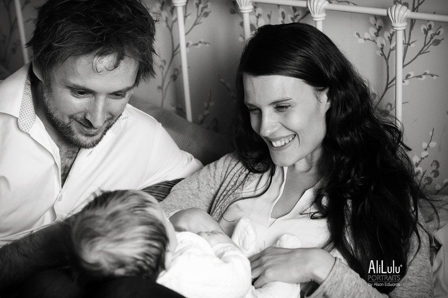 mum and dd smiling at baby