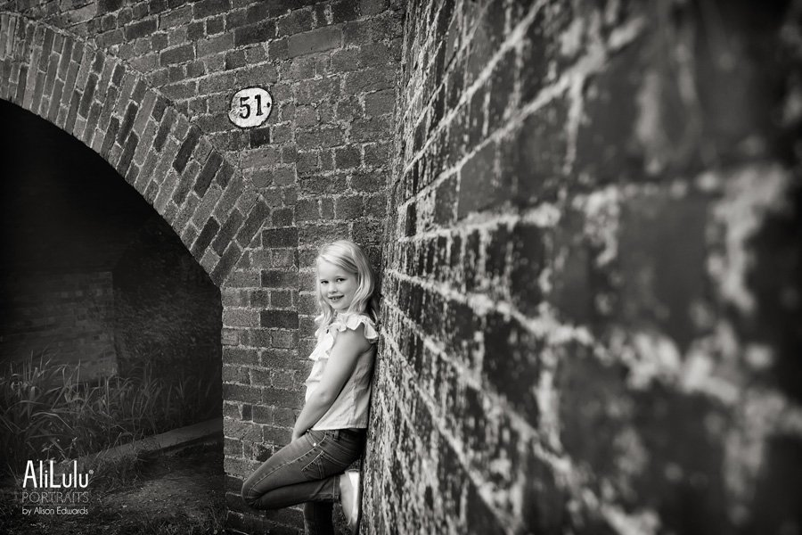 girl leaning against wall near bridge