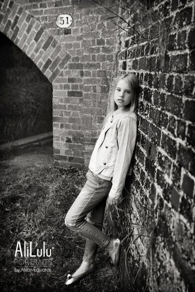 young girl leaning against wall