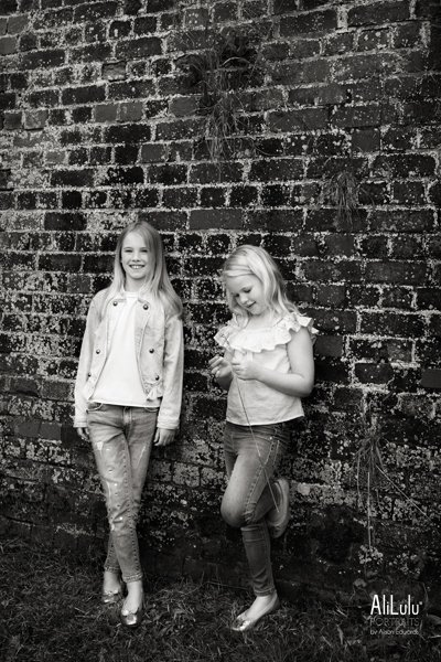 sisters leaning against brick wall